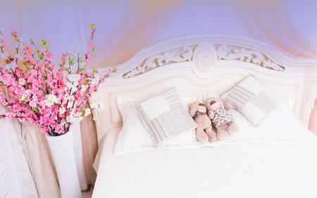 snuggling: High Angle View of Romantic Pink and White Bouquet of Flowers Beside Bed with Male and Female Couple Teddy Bears Snuggling