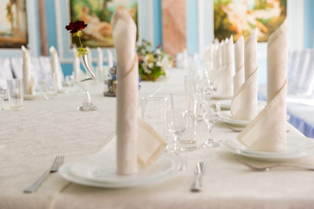 serviettes: Details of place settings on as wedding table with decorative coiled serviettes with white linen and stylish glassware Stock Photo