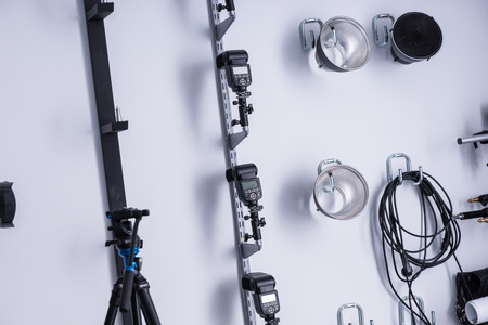 reflectors: Lighting equipment in a photographic studio neatly arranged on the wall with flash lights, cable, reflectors and a tripod