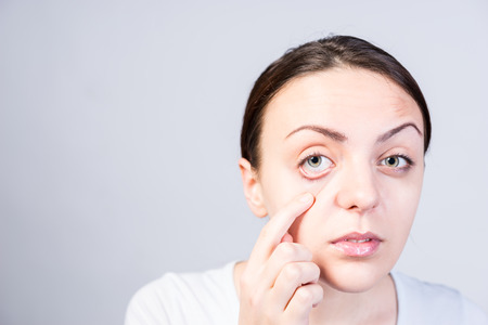 pat down: Close up Pretty Young Woman Pulling Down her Lower Eyelid While Looking at the Camera on a Very Light Gray Wall with Copy Space. Stock Photo