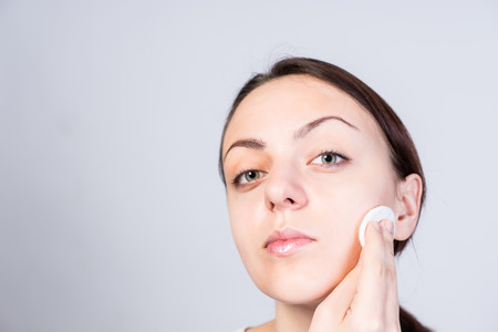unblemished: Close up Vain Young Woman Applying Astringent to Clean Face Using Cotton While Looking at the Camera. Isolated on Gray Background.