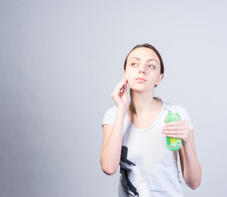 upper half: Half Body Shot of a Young Woman Scrubbing her Cheek Using Cotton with Facial Cleanser While Holding a Bottle and Looking to the Upper Left Side. Captured in Studio on a Light Gray Background.