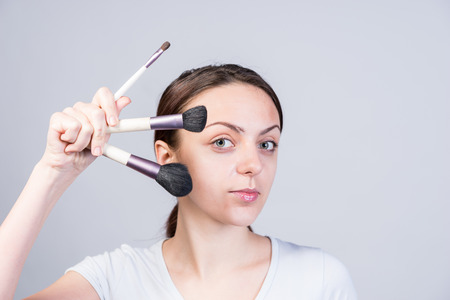 pert: Close up Young Pretty Woman Holding Makeup Brushes in Different Sizes Like a Fan While Looking at the Camera on a Gray Background.