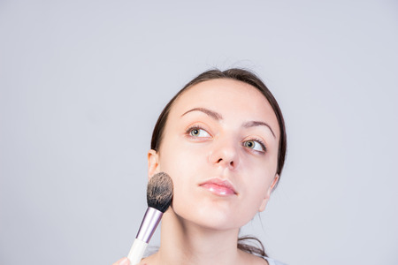 unblemished: Close up Thoughtful Young Woman Applying Makeup on Face Using Brush While Looking Afar on Upper Left Side.