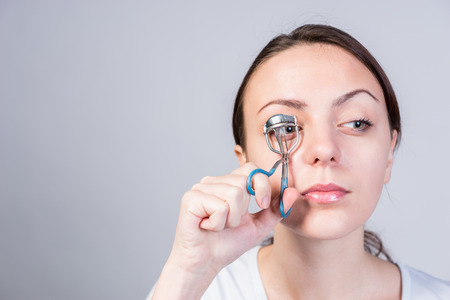 crimping: Serious Young Woman Crimping her Right Eyelashes Using Lash Curler While Looking to the Right of the Frame on a Gray Background.