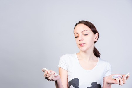 unblemished: Close up Undecided Young Woman Holding Two Foundation Make ups, Thinking which one to use, on a White Background. Stock Photo