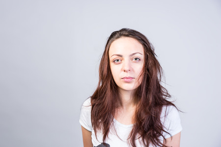 rueful: Close up Serious Young Woman With Long Messy Brown Hair Looking at Camera on a Gray Background. Stock Photo