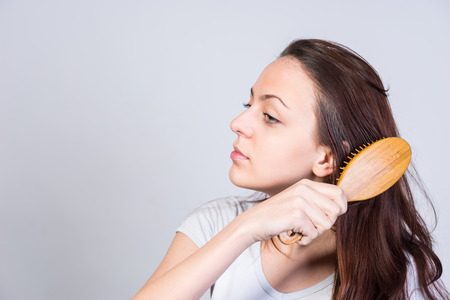 tousled: Pretty young woman brushing out her long brown hair with a stylish wooden hairbrush in a beauty and grooming concept, over grey