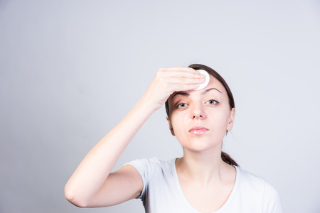 unblemished: Close up Serious Young Woman Applying Astringent on her Forehead While Looking at the Camera. Isolated on a Gray Background.