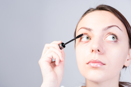 thicken: Close up Face of a Young Woman Applying Mascara Makeup While Looking to the Right on a Gray Background.