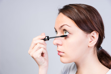 thicken: Attractive woman applying dark mascara to her eyelashes with a small applicator brush as she looks upwards with her gorgeous green eyes, side view Stock Photo