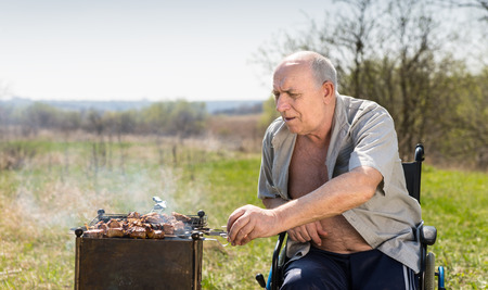 unbuttoned: Aged Man with Unbuttoned Shirt Sitting on his Wheelchair While Grilling for his Lunch Under the Heat of the Sun at the Park. Stock Photo