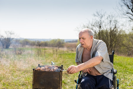 unbuttoned: Disabled Elderly Man with Unbuttoned Shirt Sitting on his Wheelchair While Grilling Some Meat Sausages to Eat at the Park Alone on a Hot Morning.