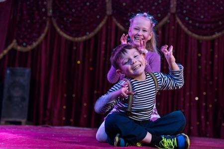 niños actuando: Dos niños juguetones divertidos, niño y niña, sonriendo mientras actúa como monstruos con garras, en un escenario de color púrpura, en una representación teatral Foto de archivo