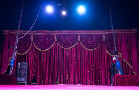 circus stage: Colorful magenta curtains on a stage with bright shining spotlights inside a tent or marquis getting ready for a performance
