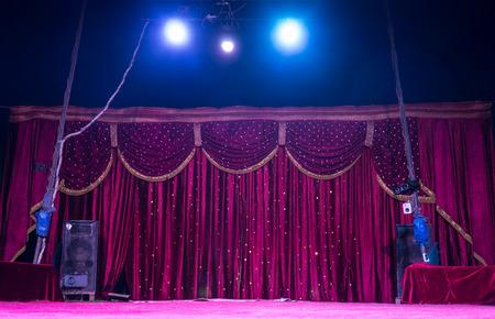 circo: Cortinas magenta coloridas en una etapa con focos brillantes brillantes dentro de una tienda de campaña o marqués preparándose para una actuación Foto de archivo