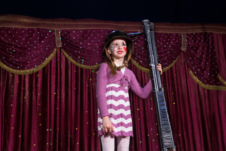 blunderbuss: Girl Wearing Striped Dress and Combat Helmet Standing on Stage Holding Barrels of Shot Gun Propped Upright on Stage with Red Curtain