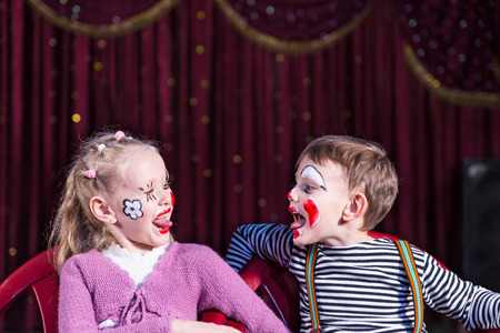 exuberant: Funny boy and girl with painted faces sticking out the tongue one to each other, while performing on stage Stock Photo