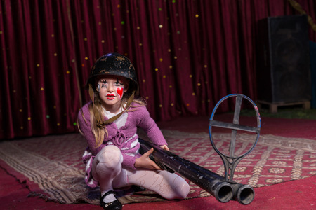 blunderbuss: Girl Wearing Combat Helmet Crouching on Ground with Large Double Barreled Shot Gun with Iron Sight on Stage with Red Curtain