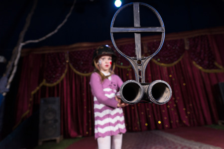 blunderbuss: Young Girl Wearing Striped Dress Holding Large Gun on Stage with Red Curtain, Focus on End of Double Barreled Shot Gun with Iron Sight