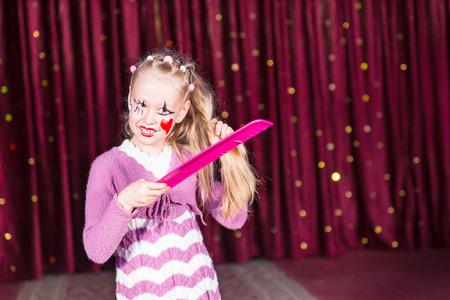pantomima: Muchacha bonita joven en un traje de pantomima rosa de pie en el escenario que se peina el pelo largo y rubio con un peine descomunal en su maquillaje y la cara de colores de pintura Foto de archivo