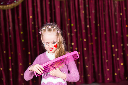 blond girl: Young Blond Girl Wearing Clown Make Up Brushing Hair with Large Pink Comb in front of Red Stage Curtain with Copy Space to the Right Stock Photo