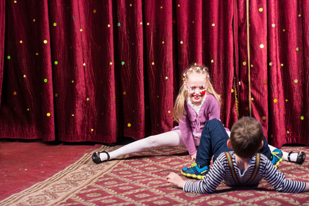 supple: Blond Girl Wearing Clown Make Up Performing Splits on Stage with Red Curtain with Young Boy in Foreground