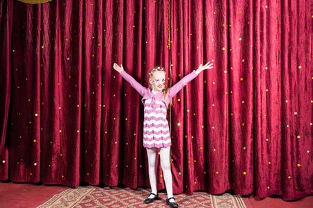 pantomima: Ni�a bastante orgullosos de pie en el escenario durante una representaci�n de una obra de teatro o pantomima con los brazos extendidos en frente de las cortinas de color burdeos cerrados Foto de archivo