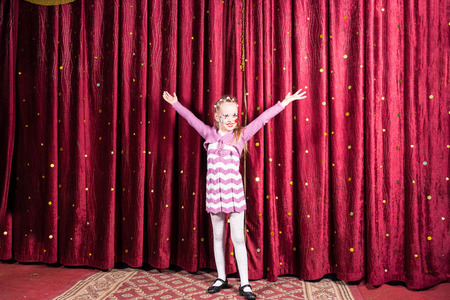 Pretty proud little girl standing on stage during a performance of a school play or pantomime with her arms outstretched in front of the closed burgundy curtains