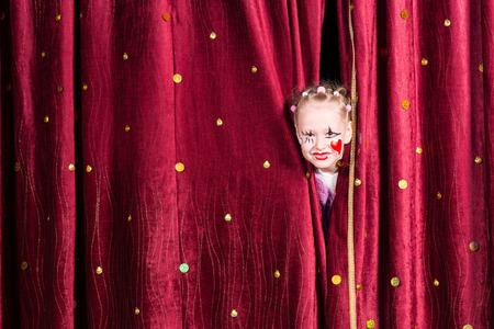pantomima: Ni�a bonita usando maquillaje colorido con un coraz�n rojo en la mejilla mirando por entre las cortinas de espera para salir en el escenario durante una pantomima