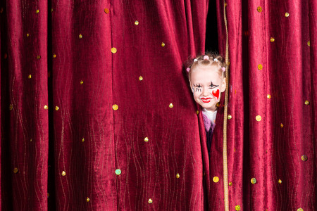 stage: Pretty little girl wearing colorful makeup with a red heart on her cheek peering out between the curtains waiting to come out on stage during a pantomime