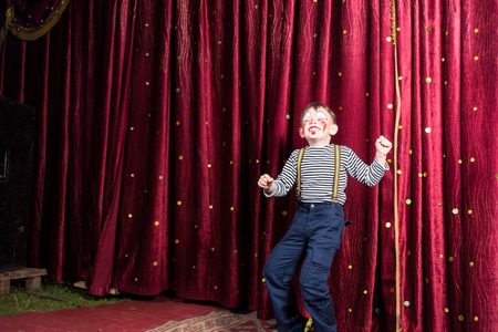 exuberant: Exuberant little boy performing on stage at a pantomime standing in front of the closed burgundy curtains doing his act in his costume and makeup with a laughing smile, with copyspace Stock Photo