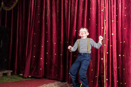 pantomima: Ni�o Exuberante realizar en el escenario en un pie pantomima delante de las cortinas de color burdeos cerrados haciendo su acto en su traje y el maquillaje con una sonrisa de risa, con copyspace Foto de archivo