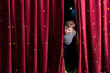 preteen boy: Anxious young boy actor in his costume and makeup looking out from the curtains on stage to check that everything is going to schedule