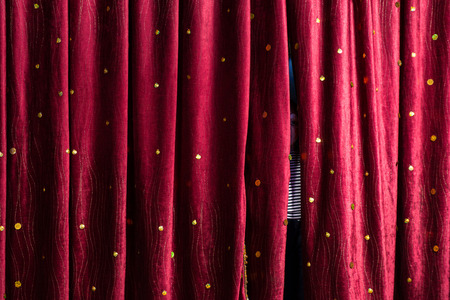 peering: Little boy lurking behind the stage curtains peering through the gap waiting for his cue to come out on stage during a performance