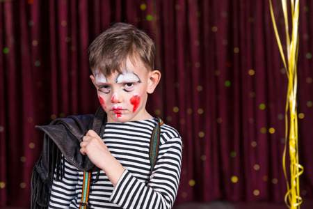 soulful: Sulky little boy wearing face paint on stage looking at the camera with a soulful sad expression as he stands in front of the curtain
