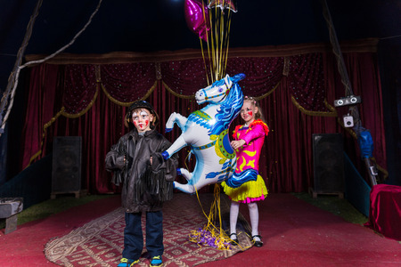 Boy Dressed as Clown Wearing Leather Jacket and Helmet Standing on Stage with Girl Wearing Bright Costume Holding Balloon Strings and Horse Shaped Balloon Stock Photo