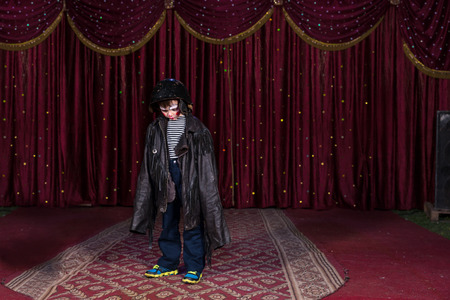 over sized: Young Boy Wearing Clown Make Up Standing on Stage in Over Sized Leather Jacket with Red Curtain in Background