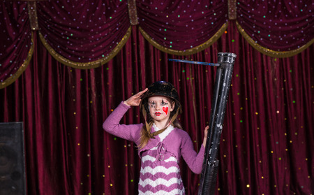 blunderbuss: Cute young girl wearing a helmet and makeup holding a blunderbuss in her hand as she salutes the camera during a pantomime performance Stock Photo