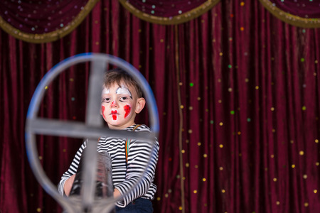 gun sight: Young Boy Dressed as Clown Wearing Make Up and Striped Shirt Looking Serious and Framed in Iron Gun Sight and Standing on Stage with Red Curtain