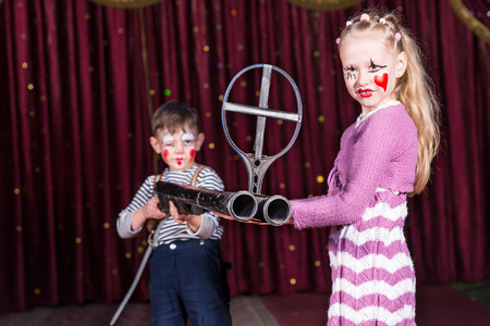 blunderbuss: Boy and Girl Dressed as Clowns Standing on Stage with Red Curtain Holding Large Double Barrel Gun with Iron Sight Stock Photo