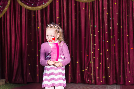 over sized: Smiling Blond Girl Wearing Clown Make Up and Striped Dress Standing on Stage Holding Over Sized Pink Comb in front of Red Curtain Stock Photo