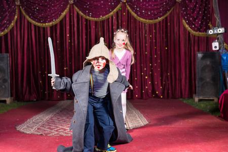 niños en la escuela: Chico talentoso lindo que juega el papel de un guerrero valiente ruso luchando con una pradera a la defensa de su bella esposa, en una representación teatral en la escuela