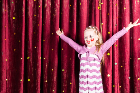 Pretty little blond girl in pantomime costume standing on stage playing to the audience with her arms outstretched and a big smile