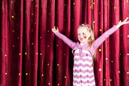 pantomima: Ni�a bonita rubia en la pantomima traje de pie en el escenario tocando a la audiencia con los brazos extendidos y una gran sonrisa