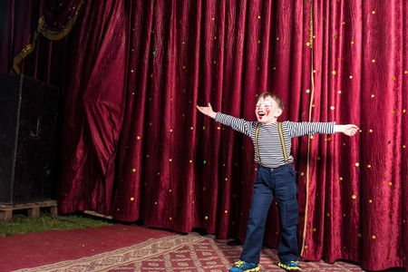 outspread: Laughing confident little boy performing on stage in a pantomime standing in his striped costume and colorful face paint with outspread arms laughing and smiling in front of the curtain