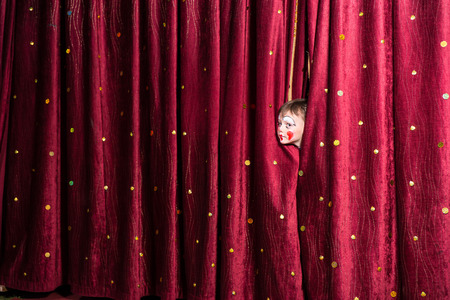 poking: Impatient little boy on stage poking his head out from between the closed curtains as he looks to see what the delay is for the start of the play or pantomime