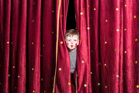 Niño pequeño lindo vistiendo coloridos pintura de la cara roja y un traje mirando por entre las cortinas en el escenario mientras espera para una pantomima para comenzar