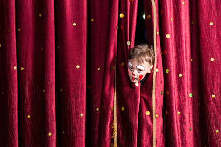 stage costume: Impatient young boy actor wearing colorful red face paint peeking out from the patterned burgundy curtains on a stage waiting for the performance to begin Stock Photo