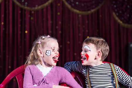 Boy and Girl Wearing Clown Make Up Sitting in Chairs Side by Side and Sticking Tongues Out at Each Other photo
